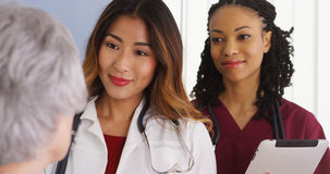 Asian woman physician and black nurse with elderly patient. Asian women physician and black nurse with elderly patient in hospital room royalty free stock images