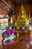 Asian woman pilgrim prostrating oneself in front of the Buddha statues in hall of Wat Tham Khao Wong Royalty Free Stock Photography