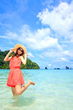 Asian woman in a pink dress standing on the beach Stock Images
