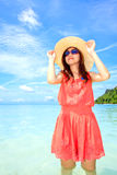 Asian woman in a pink dress standing on the beach Stock Photo