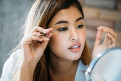 Asian woman placing decorative eyelashes on eye. Closeup young Asian model placing decorative eyelashes on eye on blurred background royalty free stock photography