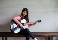 Asian Woman play with guitar Stock Photo