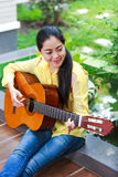 Asian woman playing classic guitar, outdoor at daytime with brig Royalty Free Stock Images