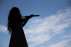 Asian Woman playing flute instrument in Silhouette shape with sk Stock Image
