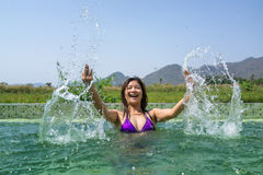 Asian woman playing and splashing in the swimming pool. Asian woman in purple bikini playing and splashing in the swimming pool with mountain and green grass Royalty Free Stock Photos