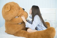 Asian woman playing with teddy bear in the bedroom. Royalty Free Stock Photo