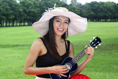Asian woman playing Ukulele Royalty Free Stock Images