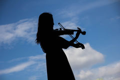 Asian Woman playing violin instrument in Silhouette shape with s Stock Photo