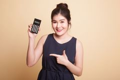 Asian woman point to  calculator. Royalty Free Stock Photo