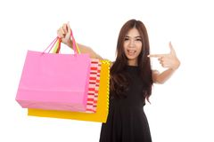 Asian woman point to shopping bags and smile Royalty Free Stock Photography