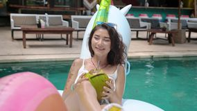 Asian woman in pool drinking a coconut fruit. Close-up of woman portrait smiling and drinking a long cocktail from coconut fruit on exotic island resort stock video