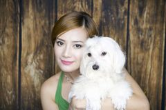 Woman Portrait with cute dog. Asian woman portrait wearing green dress with cute white dog Royalty Free Stock Image