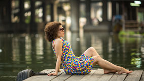 Asian  woman posing sitting on the pier near river. Stock Photo