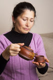 Asian woman pouring tea in cup Royalty Free Stock Photography