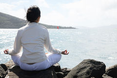 Asian woman practices Yoga. An Asian woman practices Yoga with beautiful landscape of mountains and sea Stock Images