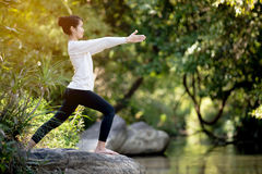 Asian woman practices yoga Stock Photography