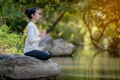 Asian woman practices yoga Stock Image