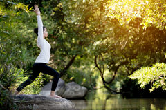 Asian woman practices yoga Royalty Free Stock Photography