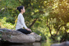 Asian woman practices yoga Royalty Free Stock Photos