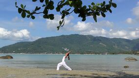 Woman Practicing Yoga at the Sea on Tropical Island. Asian Woman Practicing Yoga at the Sea on Tropical Island. Yogi Girl at the Beach in White Cloths stock video
