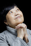 Asian woman praying and praising the Lord. In black royalty free stock photo