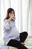 Asian woman pregnant ,pregnancy drinking fresh water in glass us Royalty Free Stock Images