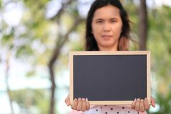 Asian women are pregnant for about twelve weeks to holding a bla. Asian woman are pregnant for about twelve weeks to holding a blank blackboard in the garden for Stock Images