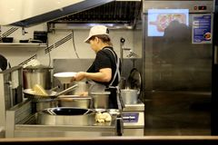 Asian woman prepares food behind a glass partition, food court at the central market. stock photography