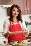 Asian Woman Preparing Food in Kitchen Stock Image