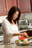 Asian Woman Preparing Food in Kitchen Stock Photo