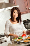 Asian Woman Preparing Food in Kitchen Stock Photography