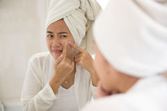 Asian woman pressing acne on her cheek Stock Images