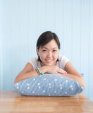Asian woman put the hand on a  blue polkadot  pillow and smiling Stock Images