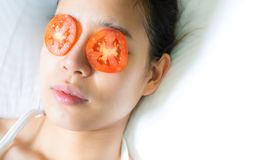 An asian woman put pieces of tomato on her eyes stock photography