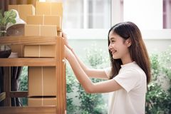 Asian woman put sticky memo paper note on parcel mail box and re. Ady to send to customer. Business owner and Online shopping concept. Post office delivery and stock photo