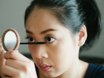 Woman is putting make up mascara on her eyelashes. Asian woman is putting make up mascara on her eyelashes royalty free stock image