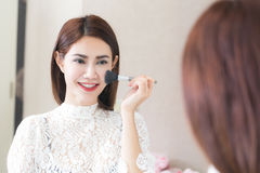 Asian woman putting makeup in home using a contour brush to apply blonze powder under cheek bones make-up mirror. stock photos