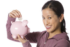 Asian woman putting money into a piggy bank Stock Image