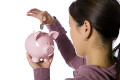 Asian woman putting money into a piggy bank Royalty Free Stock Image