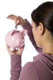 Asian woman putting money into a piggy bank Royalty Free Stock Photos