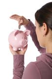 Asian woman putting money into a piggy bank Stock Photos