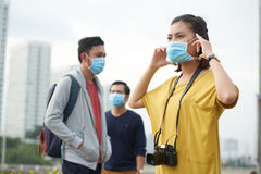 Asian woman putting on protective mask Royalty Free Stock Photo