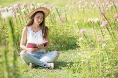 Asian woman read book on flower field. Portrait of Happy beautiful Asian woman with hat holding book to read and sit on grass field with flowers in morning Royalty Free Stock Photos