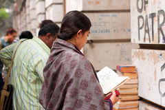 Asian woman read the book near the street book stall Stock Image