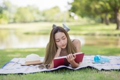 Asian woman read book at park. Attractive Asian beautiful girl reading text book and lying down on mat at field near pond. Outdoor education lifestyle concept royalty free stock image