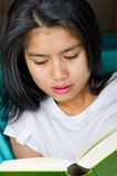 Asian woman reading a book Stock Images