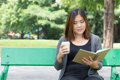 Asian woman reading a book and holding coffee cup in the park Stock Image
