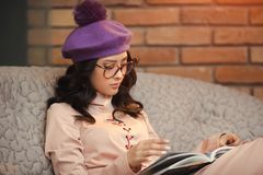 Asian woman reading book indoors. Woman studying at home. Portrait of attractive happy asian girl reading book and sitting on sofa indoors against brick wall Royalty Free Stock Photos