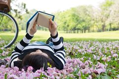 Asian woman reading booklet. On the grass stock photo