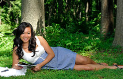 Asian woman reading a magazine in park Stock Photography